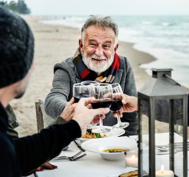 Senioren, die mit rotwein am strand rösten Premium Fotos