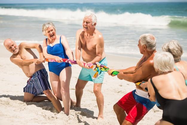Senioren, die tauziehen am strand spielen Premium Fotos