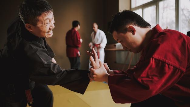 Sensei zeigt dem schüler, wie er seinen arm ringt. Premium Fotos