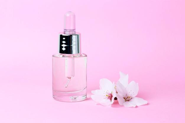 Serum und tropfenzähler auf einer rosa hintergrundnahaufnahme, naturkosmetikkonzept Premium Fotos