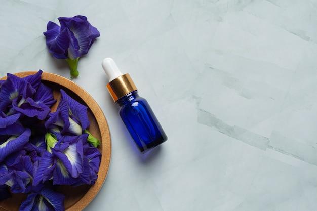 Serumflasche butterfly pea flower oil auf weißem marmorhintergrund Kostenlose Fotos