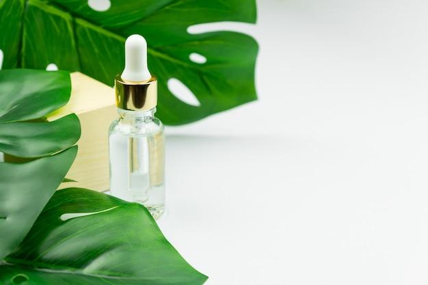 Serumflasche nahe palmblatt. trendiges schönheitsprodukt für junge haut. Premium Fotos