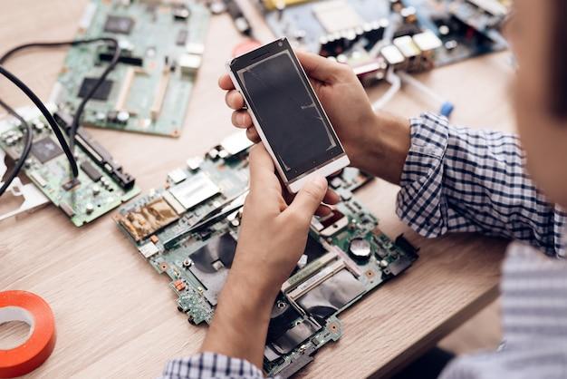 Service-arbeiter halten in der hand und sieht defektes telefon aus Premium Fotos