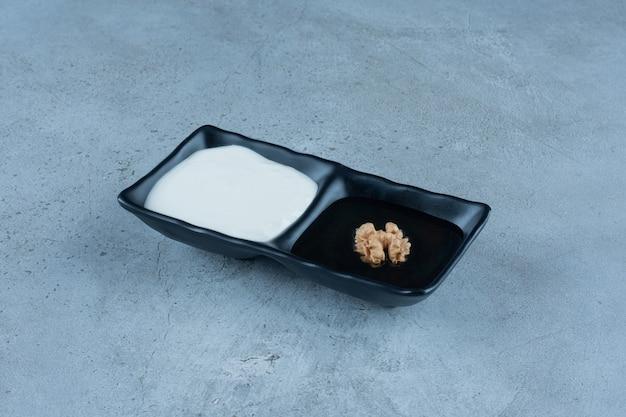 Servierplatte mit portionen sahne und honig auf marmor. Kostenlose Fotos