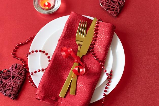 Serviertisch mit gabel, messer, serviette und herzdekoration zum valentinstag. abendessen am valentinstag. Premium Fotos