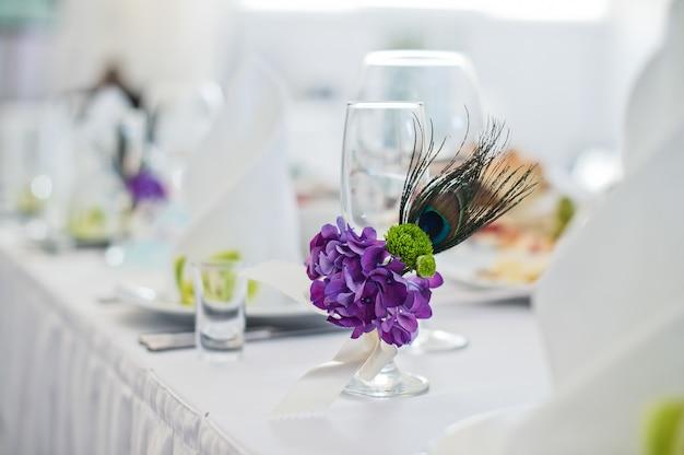 Serviertisch mit tellern, weißen servietten und gläsern mit lila blüten, abendessen im restaurant Premium Fotos