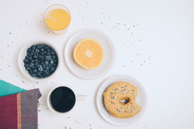 Serviette; blaubeere; ein glas saft; halbierte orange; kaffeetasse und donut auf weißem hintergrund Kostenlose Fotos