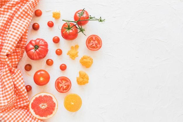 Serviette mit gemüse und früchten auf weißem strukturiertem hintergrund Kostenlose Fotos