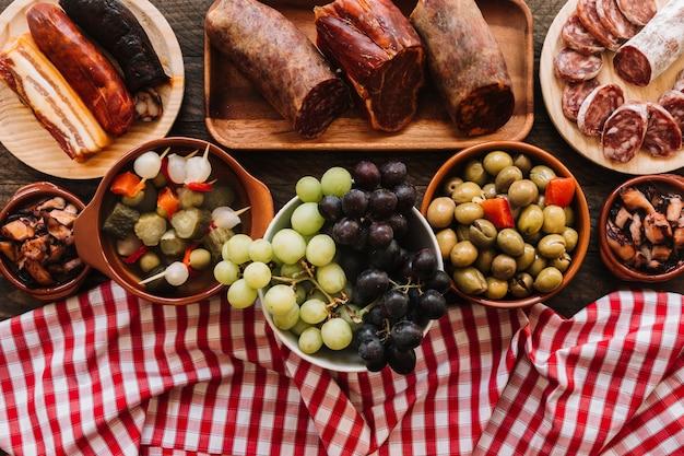 Serviette und trauben nahe essiggurken und würsten Kostenlose Fotos