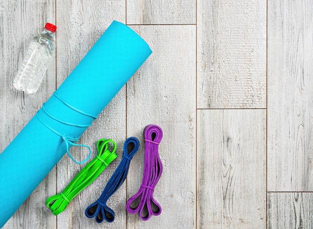 Set aus hellen latex-gummibändern für fitness, yogamatte und eine flasche wasser Kostenlose Fotos