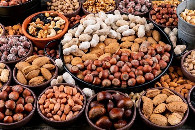 Set aus pekannüssen, pistazien, mandeln, erdnüssen, cashewnüssen, pinienkernen und verschiedenen nüssen und getrockneten früchten in verschiedenen schalen. seitenansicht. Kostenlose Fotos