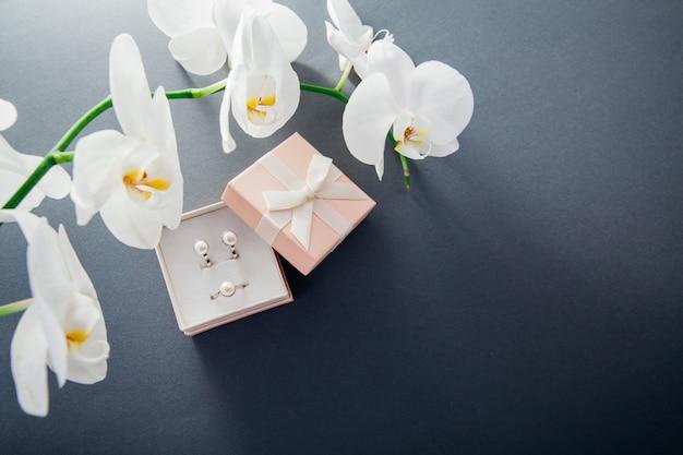Set aus silbernem ring und ohrringen mit perlen in der geschenkbox mit weißer orchidee Premium Fotos