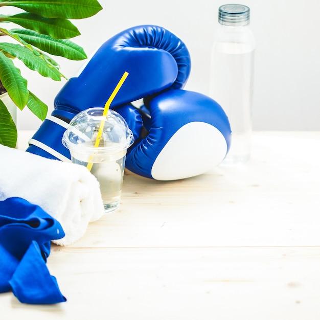 Set für sport, handtuch, boxhandschuhe und eine flasche wasser für einen leichten, gesunden lebensstil. Premium Fotos