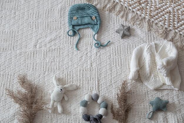 Set stilvolle handgefertigte strickkleidung für kinder mit verschiedenen accessoires im boho-stil, draufsicht. Kostenlose Fotos