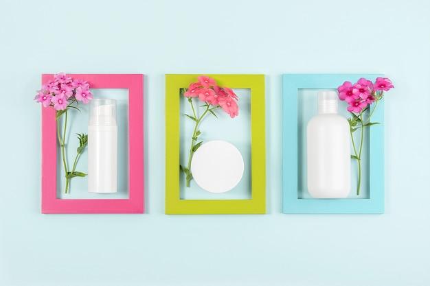 Set von kosmetika für hautpflege gesicht, körper, hände. weiße leere kosmetikflasche, tube, glas, blumen in hellen rahmen auf blau Premium Fotos