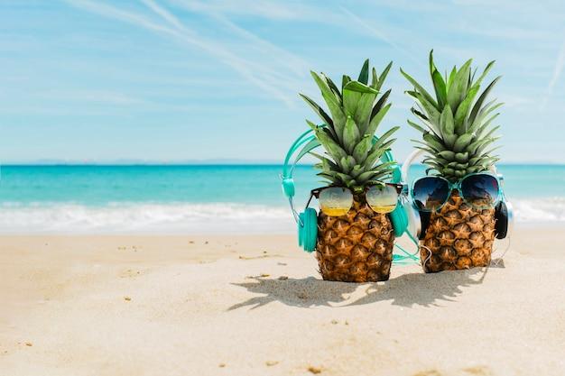 Setzen sie hintergrund mit den kühlen ananas auf den strand, die kopfhörer tragen Kostenlose Fotos
