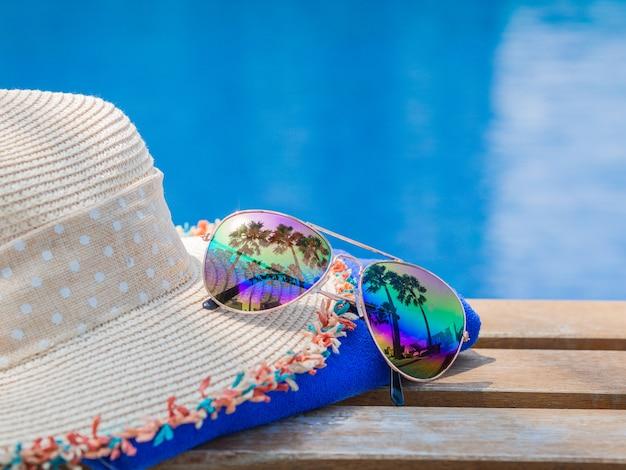Setzen sie hut mit sonnenbrille an der seite des swimmingpools für sommerkonzept auf den strand Premium Fotos