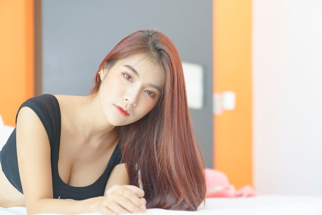 Sexy asiatische frau im schwarzen bikini, die auf dem bett liegt Premium Fotos