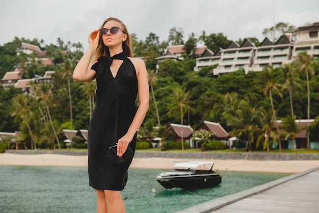 Sexy attraktive luxusfrau gekleidet im schwarzen kleid, das auf pier im luxusresorthotel aufwirft, sonnenbrille tragend, sommerferien, tropischer strand Kostenlose Fotos