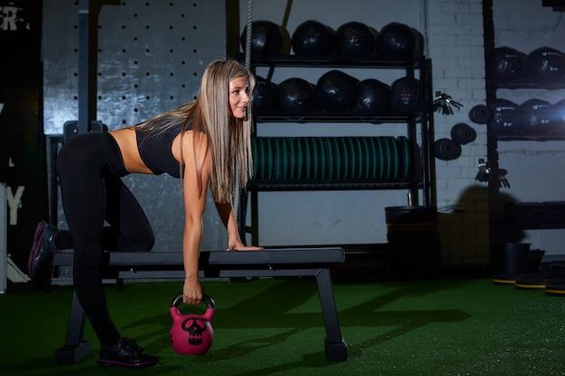 Sexy blonde athletische frau in den schwarzen festen gamaschen, die übung auf bank mit gewicht cross-fit in der turnhalle tun Premium Fotos