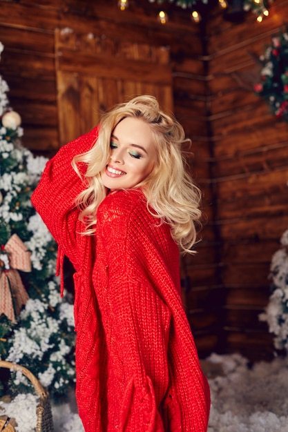 Sexy blondes mädchen in der roten strickjacke, spaß habend Premium Fotos