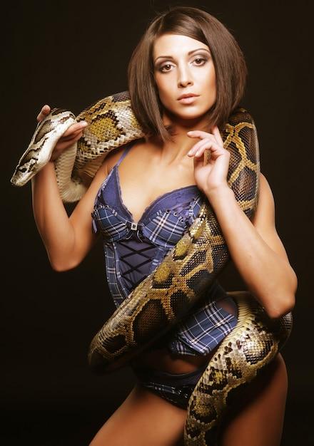 Sexy brünette hält python über schwarz Premium Fotos