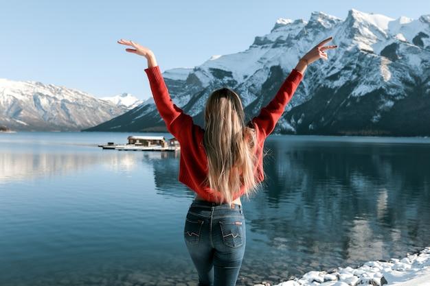 Sexy dame mit schlankem perfektem körper, der am strand nahe dem wintersee steht. weißer schnee liegt auf dem boden und auf den gipfeln der berge. langes blondes haar, das auf der rückseite des roten pullovers liegt. Kostenlose Fotos