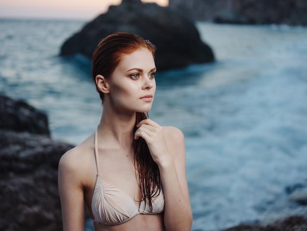 Sexy frau in einem badeanzug am strand nahe dem meer in der natur gestikuliert mit ihren händen. Premium Fotos