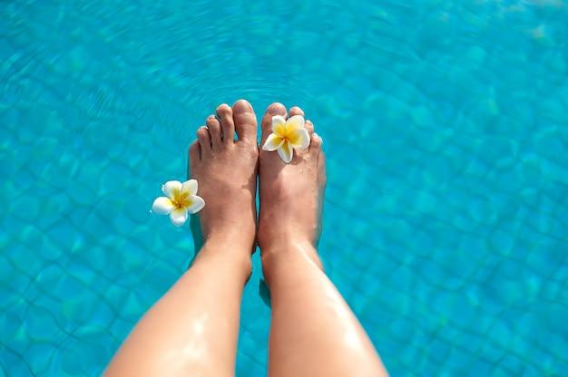 Sexy frauenbein-pedikürenägel, die im tropischen schwimmensommerpool spritzen Premium Fotos