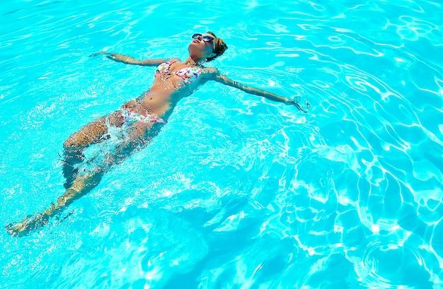 Sexy heißes schönes mädchenmodell mit dunklem haar in der bunten badebekleidung, die auf rücken schwimmt Kostenlose Fotos