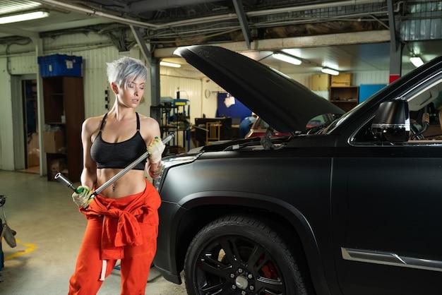 Sexy junge frau, die das auto in einem autoservice repariert Premium Fotos