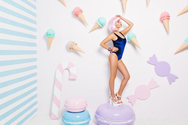 Sexy junge frau im blauen body, auf den fersen, mit rosa geschnittener frisur, die auf großem macaron unter süßigkeiten steht. freudiges model, entspannung, süßer lebensstil, geschlossene augen. Kostenlose Fotos