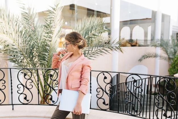 Sexy junge frau, student mit silbernem laptop stehend auf schönem balkon, terrasse im hotel, restaurant mit palmen im hof. tragen sie eine stilvolle brille, eine rosa jacke, eine beige bluse und eine süße frisur. Kostenlose Fotos