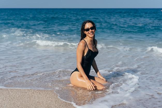 Sexy junger brunette, der auf ihren knien im meer aufwirft Kostenlose Fotos