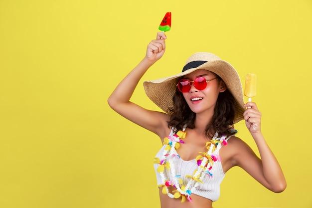 Sexy mädchen hält wassermelone und mango-eis, während brille und hut im sommer heißes wetter auf gelber wand tragen. Kostenlose Fotos