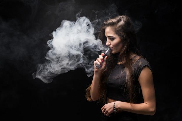 Sexy mädchen in einem schwarzen kleid, das elektronische zigarette auf dunkler wand raucht Kostenlose Fotos