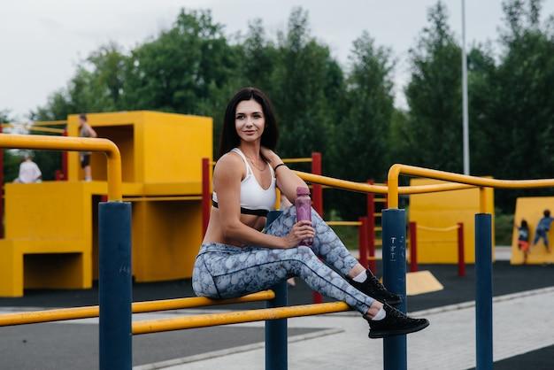 Sexy mädchen macht sport und trinkt wasser im freien
