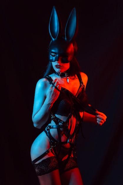 Sexy mädchen modell in hasenmaske in dessous mit ledergürtel mit peitsche in den händen Premium Fotos