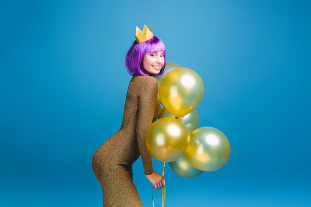 Sexy schöne junge frau im modischen luxuskleid, das spaß mit goldenen luftballons hat. schneiden sie lila haare, krone, feiern neujahrsparty, geburtstag, lächeln, glück. Kostenlose Fotos