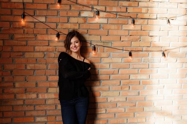 Sexy schönheit in der schwarzen strickjacke und in jeans, die nahe einer retro- wand des roten backsteins stehen Kostenlose Fotos