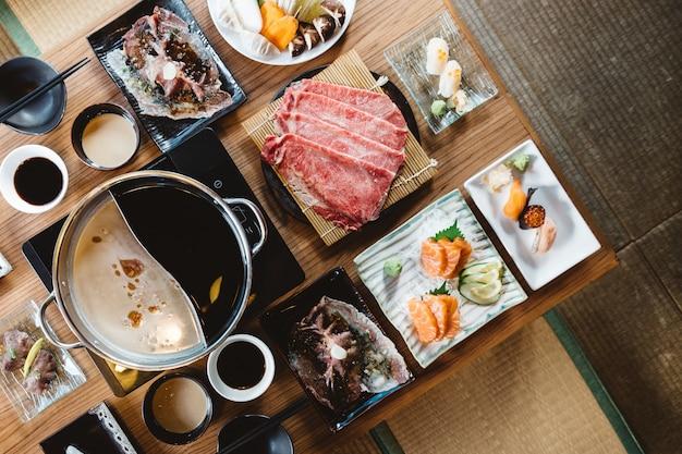 Shabu-set mit seltenen scheiben wagyu a5, shabu shoyu und klarer basis, lachs, sushi. Premium Fotos