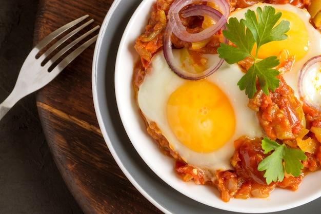 Shakshuka, ein traditionelles israelisches gericht. sonnenseitiges ei mit gedünsteten tomaten. Premium Fotos