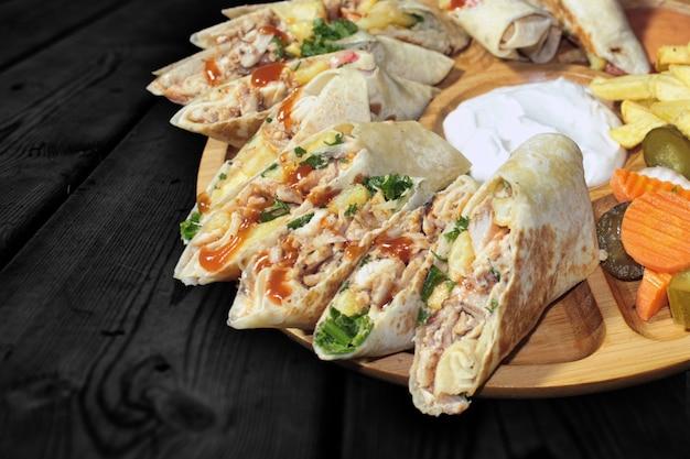 Shawarma aus hühnchen, truthahn, rindfleisch, kalbfleisch oder gemischtem fleisch auf schwarzem holztisch Premium Fotos