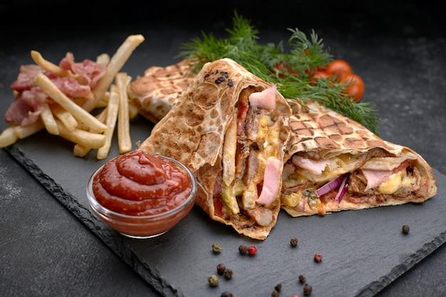 Shawarma-fleisch mit speck, kartoffeln, kräutern, tomaten und soße, auf einem schwarzen hintergrund Premium Fotos