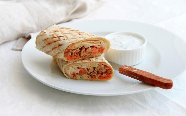 Shawarma mit fleisch in einer weißen platte Premium Fotos
