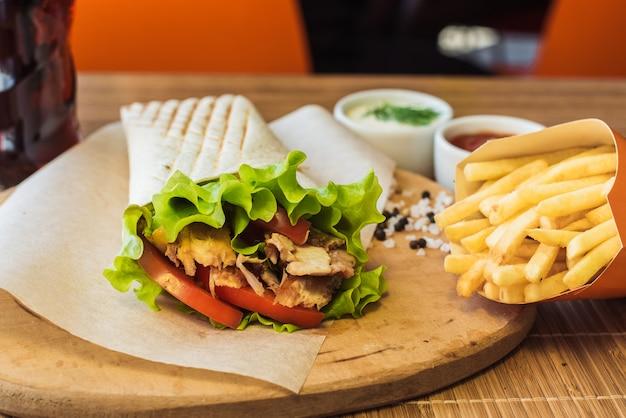 Shawarma und pommes-frites auf einem hölzernen brett in einem restaurant. tortilla mit einem getränk in einem café. Premium Fotos