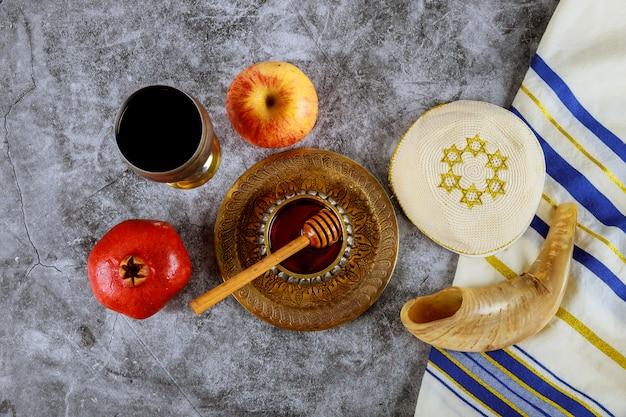 Shofar und tallit mit honigglas und frischen reifen äpfeln. jüdische symbole des neuen jahres. rosch haschana Premium Fotos