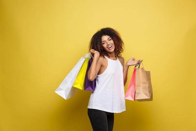 Shopping-konzept - close up portrait junge schöne attraktive afrikanische frau lächelnd und freudig mit bunten einkaufstasche. gelbe pastellwand hintergrund. text kopieren Kostenlose Fotos