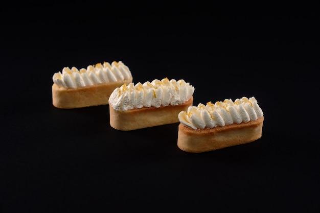 Shortbread-kekskekse mit schlagsahne-mascarpone-belag. drei frische hausgemachte desserts lokalisiert auf schwarzem hintergrund. konzept der süßigkeiten, lebensmittelindustrie. Premium Fotos