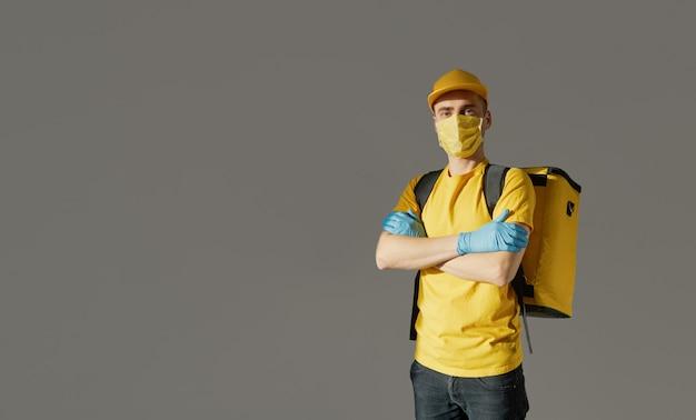 Sichere lebensmittellieferung. kurier in gelber uniform, schutzmaske und handschuhen liefert essen zum mitnehmen während der coronovirus-quarantäne. kopieren sie platz für text Premium Fotos